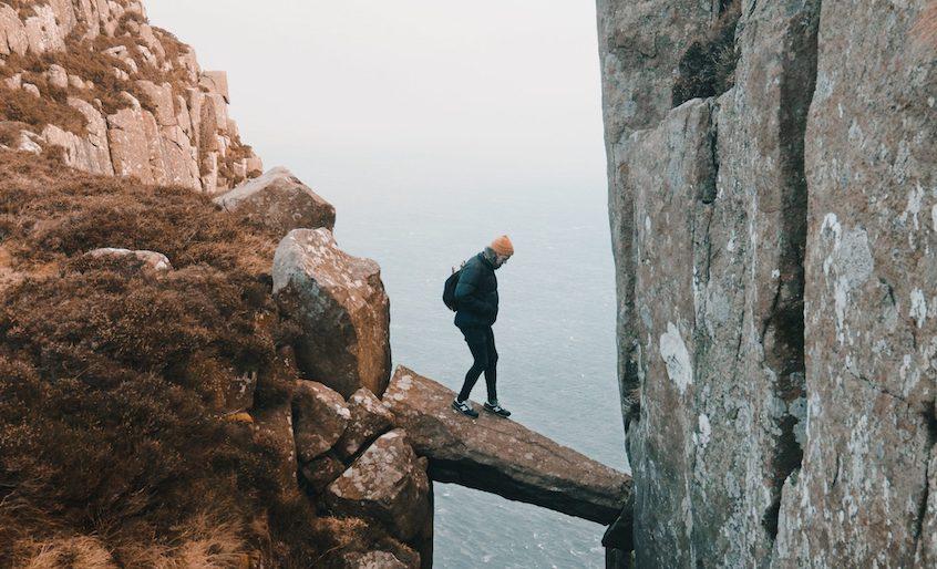 man-walking-over-rock-ledge-understanding-risks-of-alternative-investments