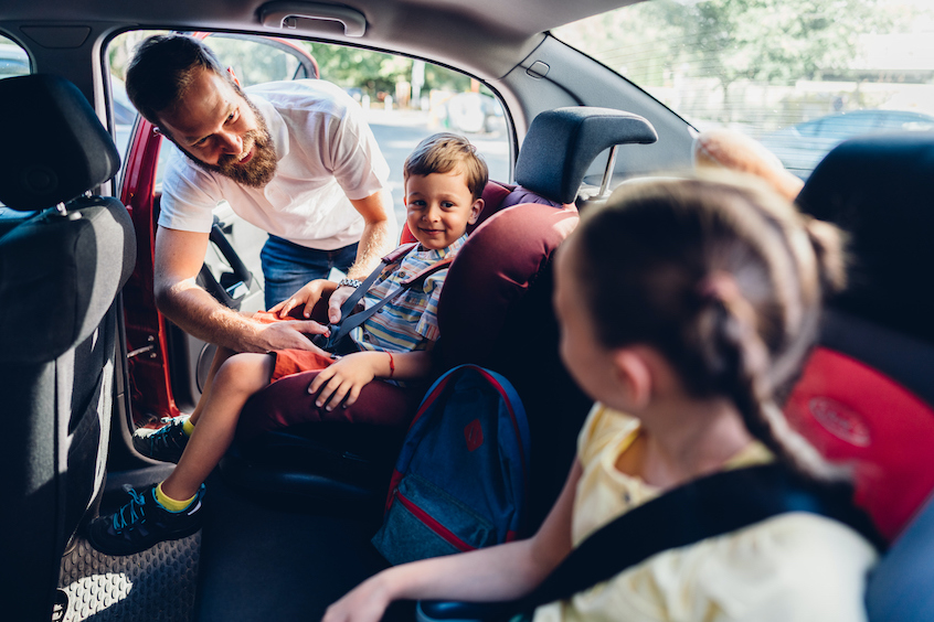 dad-strapping-kids-seatbelt-on-creating-passive-income.