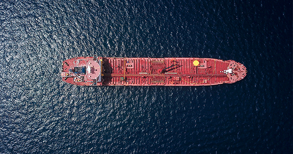 A large red cargo ship on the open ocean meant to highlight marine finance concepts in alternative investments