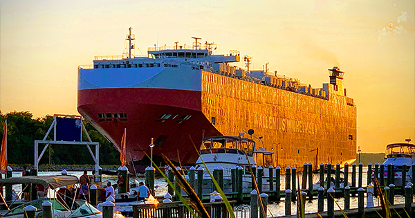 An ultramax cargo ship that could be part of a marine finance portfolio at sunset dwarfing onlookers