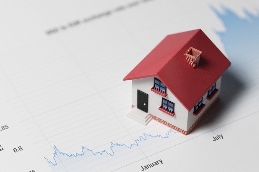 Miniature House on A Blue Financial Graph- real-estate-vs.-stocks