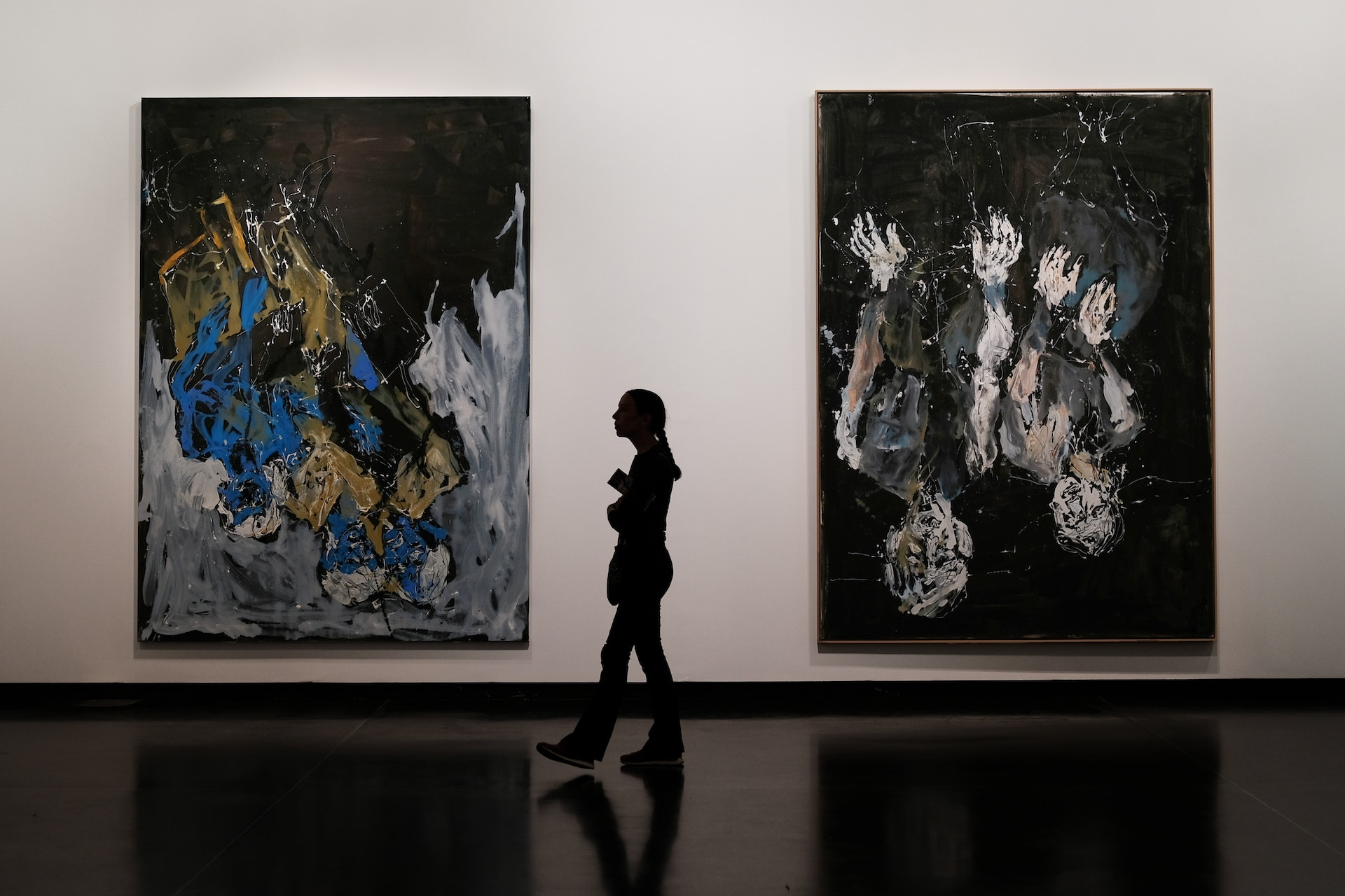 Woman walking through an art gallery meant to highlight alterntive investment opportunities in art finance