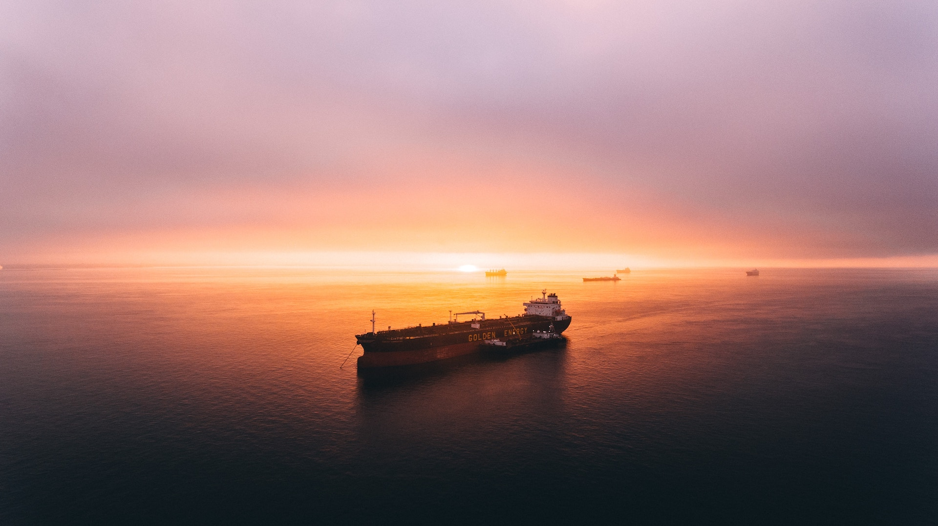 A cargo ship on the ocean at sunset meant to highlight marine finance, another alternative asset class