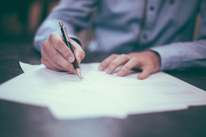 man-signing-paperwork-solo-401k-CARESAct
