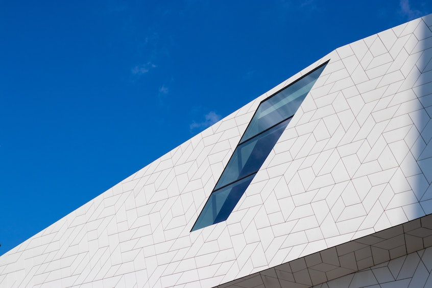 Modern architecture against blue sky meant to highlight debt investing concept in commercial real estate