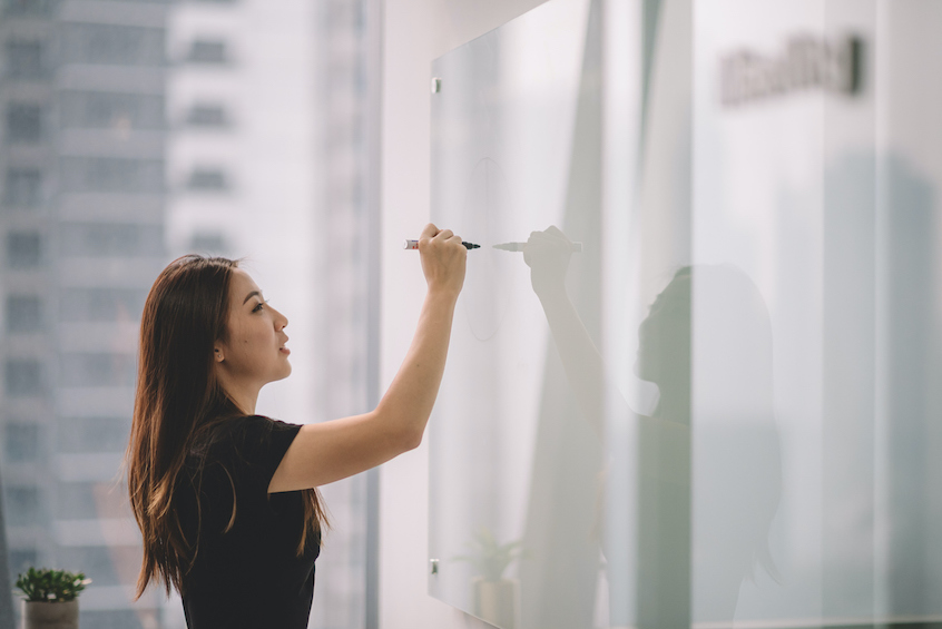 woman-writing-on-whiteboard-in-office-lifecylce-of-yieldstreet-investment