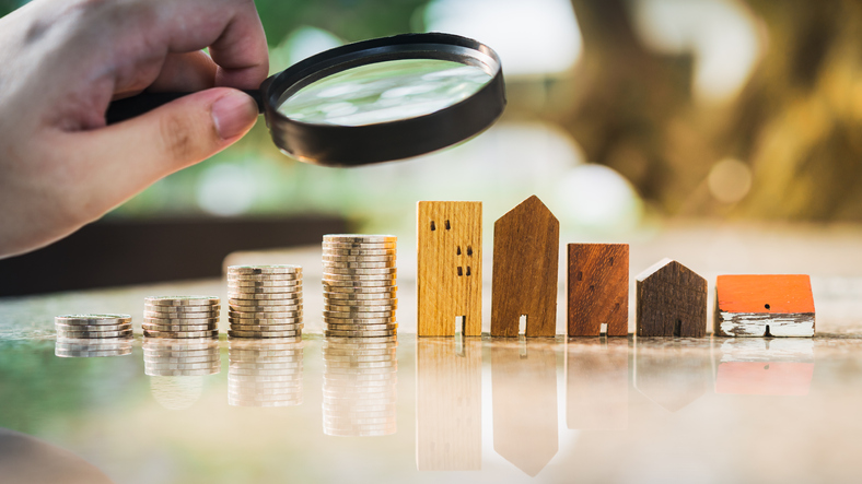 Examining house model with row of coin money, house selection, commercial real estate investing concept.