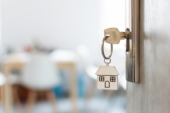 Key with keychain in a house shape in the door keyhole meant to highlight real estate market and appetite