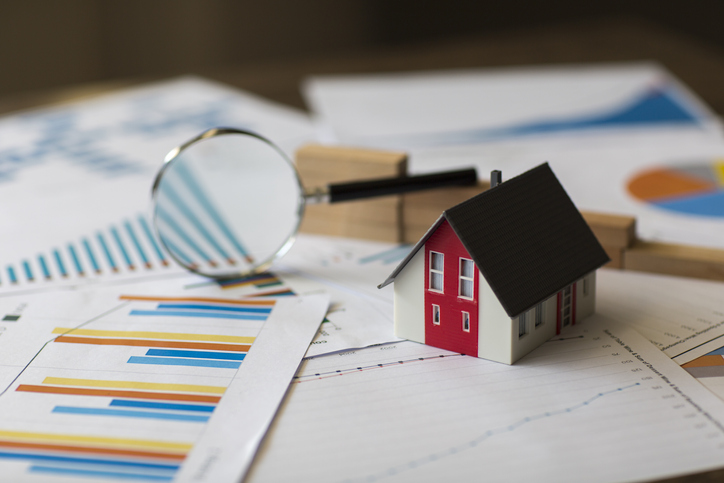 Miniature House and magnifying glass on A Financial Graph meant to highlight real estate investing concepts