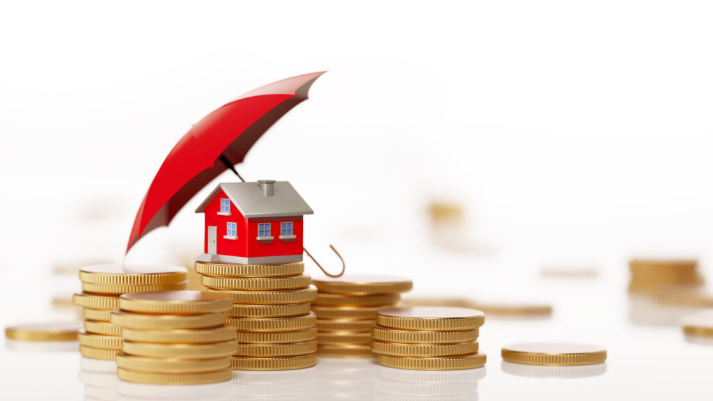 Red toy house is sitting behind  a coin stack under a red umbrella. Horizontal composition with selective focus and copy space. Real Estate and Insurance Concept.